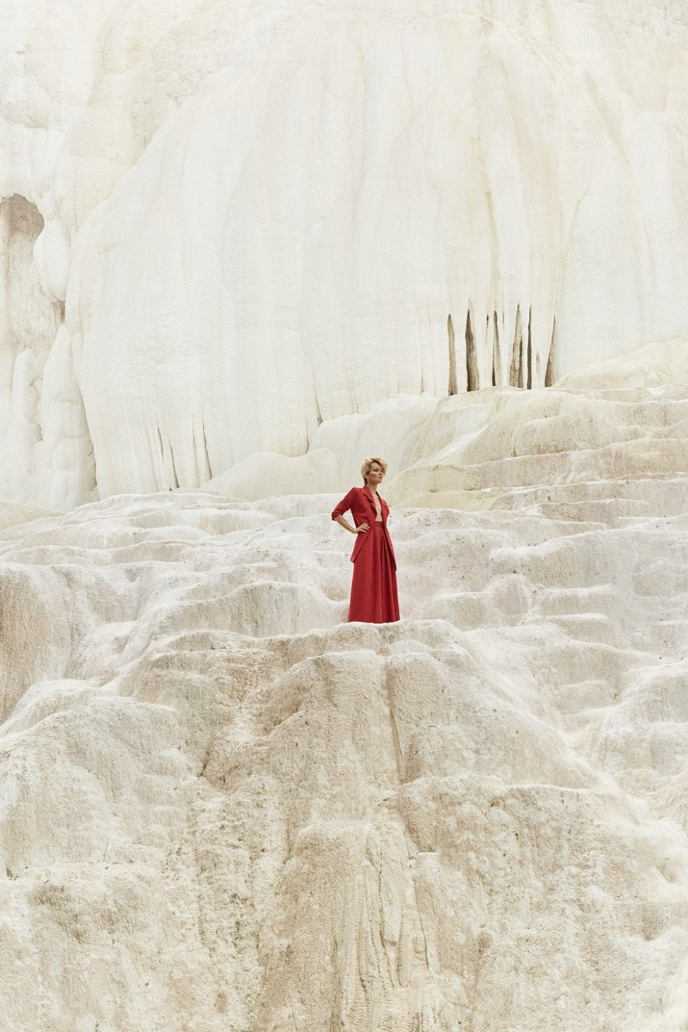 Woman is standing in abstract surrounding in red suit. Surrounding is white rock.